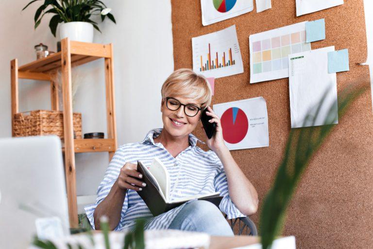 cheerful woman eyeglasses poses office talks phone